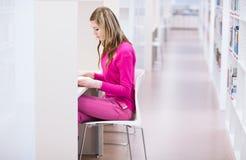 Θηλυκός φοιτητής πανεπιστημίου σε μια βιβλιοθήκη Στοκ Φωτογραφία