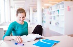 Θηλυκός φοιτητής πανεπιστημίου σε μια βιβλιοθήκη στοκ φωτογραφίες