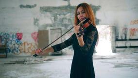 Θηλυκός φορέας βιολιών σε ένα εγκαταλειμμένο κτήριο απόθεμα βίντεο