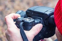 Θηλυκός φωτογράφος που κοιτάζει στο σκόπευτρο στοκ φωτογραφίες