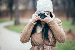 Θηλυκός φωτογράφος που παίρνει τις εικόνες υπαίθρια με μια εκλεκτής ποιότητας κάμερα στοκ εικόνες