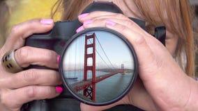 Θηλυκός φωτογράφος που φωτογραφίζει τη χρυσή γέφυρα πυλών απόθεμα βίντεο