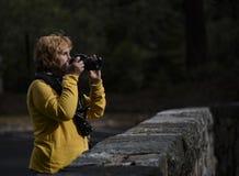 Θηλυκός φωτογράφος στο ελαφρύ κοίταγμα πρωινού πέρα από την κορυφή της κάμερας στοκ εικόνες