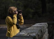 Θηλυκός φωτογράφος στο φως πρωινού με τη κάμερα μέχρι το πρόσωπό της στοκ φωτογραφίες