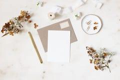 Θηλυκός χειμερινός γάμος, σκηνή προτύπων χαρτικών γενεθλίων Η κενή ευχετήρια κάρτα, φάκελος του Κραφτ, χρυσή μάνδρα, ξεραίνει στοκ φωτογραφία