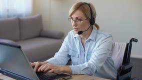 Θηλυκός χειριστής τηλεφωνικών κέντρων που εργάζεται με τη δακτυλογράφηση πελατών στο lap-top, με ειδικές ανάγκες γυναίκα απόθεμα βίντεο