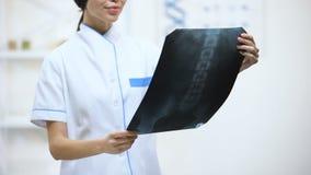 Θηλυκός χειρούργος που εξετάζει τη νωτιαία ακτίνα X, ευτυχή με το αποτέλεσμα εξέτασης ασθενών απόθεμα βίντεο