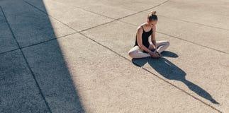 Θηλυκός χορευτής μπαλέτου που θερμαίνει πριν από την πρακτική Στοκ Φωτογραφία