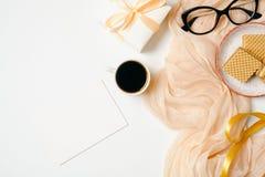 Θηλυκός χώρος εργασίας με την κενή κάρτα εγγράφου, μαντίλι, χρυσά εξαρτήματα, γυαλιά, κορδέλλα, κιβώτιο δώρων, φλυτζάνι καφέ στο  στοκ εικόνες