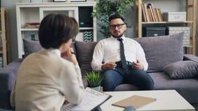 Θηλυκός ψυχολόγος που μιλά στον αρσενικό υπομονετικό επιχειρηματία κατά τη διάρκεια της συνόδου στην αρχή απόθεμα βίντεο