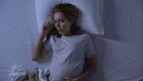 Θηλυκός expectant που βρίσκεται στο κρεβάτι που αισθάνεται τη ναυτία, ασθένεια πρωινού, υγεία εγκυμοσύνης απόθεμα βίντεο