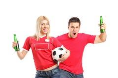 θηλυκό αρσενικό εκμετάλλευσης ποδοσφαίρου ανεμιστήρων μπυρών Στοκ Φωτογραφίες