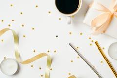Θηλυκό γραφείο τοπ άποψης με τα εξαρτήματα φλυτζανιών και κομμάτων καφέ: κορδέλλα, άχυρο ποτών, κιβώτιο δώρων, κεριά στο άσπρο υπ στοκ εικόνες
