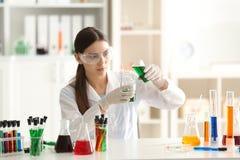Θηλυκό δείγμα χρώματος μείωσης επιστημόνων στη φιάλη δοκιμής στο εργαστήριο στοκ εικόνα με δικαίωμα ελεύθερης χρήσης