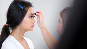 Θηλυκό ενθουσιώδες επαγγελματικό visagist που κάνει brow makeup το φρύδι καθορισμού που χρησιμοποιεί το πήκτωμα χρώματος φιλμ μικρού μήκους