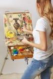 Θηλυκό ζωγράφων με το ξύλινες sketchbook και τη ζωγραφική Στοκ Φωτογραφίες