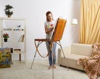 Θηλυκό ζωγράφων με το ξύλινες sketchbook και τη ζωγραφική Στοκ Εικόνες