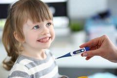 Θηλυκό θερμόμετρο εκμετάλλευσης χεριών που μετρά το άρρωστο μικρό κορίτσι στοκ εικόνες με δικαίωμα ελεύθερης χρήσης