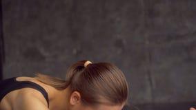 Θηλυκό ικανότητας που κάνει να τεντώσει workout στο χαλί άσκησης στο σπίτι Νέα γυναίκα που ασκεί στο χαλί ικανότητας στο καθιστικ φιλμ μικρού μήκους