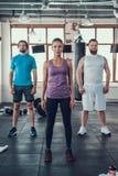 Θηλυκό και δύο αρσενικά που θέτουν στη κάμερα στη γυμναστική στοκ εικόνες με δικαίωμα ελεύθερης χρήσης