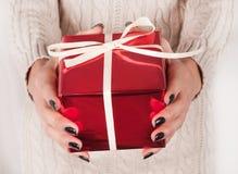 Θηλυκό κιβώτιο δώρων εκμετάλλευσης κόκκινο στα χέρια με τα μαύρα καρφιά και το πουλόβερ Στοκ φωτογραφία με δικαίωμα ελεύθερης χρήσης