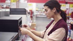 Θηλυκό κοστούμι που επιλέγει το νέο εκτυπωτή στο τμήμα ηλεκτρονικής στο κατάστημα συσκευών Ερχομός μέχρι μια σειρά προθηκών και απόθεμα βίντεο