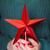 Θηλυκό κόκκινο αστέρι Χριστουγέννων χεριών εκμετάλλευσης διαθέσιμο για το δέντρο ανώτατων chistmas κλείστε επάνω Χριστούγεννα εύθ Στοκ Εικόνα