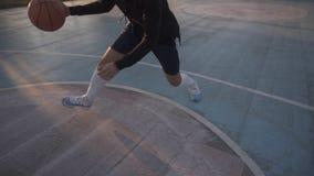 Θηλυκό παίχτης μπάσκετ στα σορτς και τις άσπρες κάλτσες στο επαγγελματικό δικαστήριο που τρέχει με τη σφαίρα και την επιτυχώς tho φιλμ μικρού μήκους