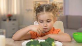 Θηλυκό παιδί που αρνείται να φάει το μπρόκολο, που ρίχνει το λαχανικό μακριά, διατροφή βιταμινών απόθεμα βίντεο