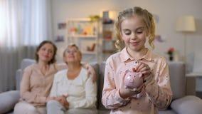 Θηλυκό παιδί που βάζει το νόμισμα piggybank, τη συνεδρίαση γιαγιάδων και μη απόθεμα βίντεο
