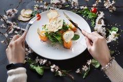 Θηλυκό πιάτο εστιατορίων κατανάλωσης στο άσπρο πιάτο στο γκρίζο υπόβαθρο Στοκ Φωτογραφίες