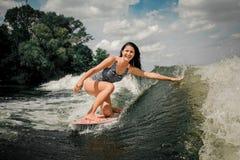 Θηλυκό που ανυψώνει επάνω πολλούς παφλασμούς από το wakeboard Στοκ Φωτογραφίες
