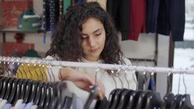Θηλυκό που επιλέγει το νέο φόρεμα σε ένα κατάστημα απόθεμα βίντεο