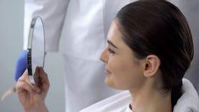 Θηλυκό που κοιτάζει στον καθρέφτη μετά από την καλλυντική διαδικασία, ικανοποίηση με το αποτέλεσμα στοκ εικόνες