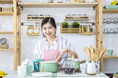 Θηλυκό που κρατά ένα κουτάλι στην κουζίνα Το πορτρέτο ενός όμορφου κουταλιού εκμετάλλευσης γυναικών έκανε τα υγιή τρόφιμα στην κο στοκ εικόνες