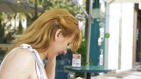 Θηλυκό που κρατά ένα smartphone στην οδό κάθισμα σε έναν θερινό καφέ φιλμ μικρού μήκους