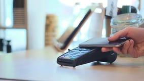 Θηλυκό που πληρώνει μέσω του έξυπνου τηλεφώνου που χρησιμοποιεί την τεχνολογία NFC Κινηματογράφηση σε πρώτο πλάνο 4K απόθεμα βίντεο