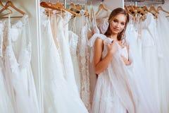 Θηλυκό που προσπαθεί στο γαμήλιο φόρεμα στοκ φωτογραφία
