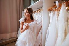 Θηλυκό που προσπαθεί στο γαμήλιο φόρεμα στοκ εικόνα