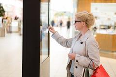 Θηλυκό που στέκεται στη μεγάλη επίδειξη με την προηγμένη καινοτόμο συσκευή Στοκ φωτογραφία με δικαίωμα ελεύθερης χρήσης
