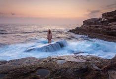 Θηλυκό που στέκεται στο βράχο ναυαγίου με τον ωκεανό awash που ρέει πέρα από το στοκ φωτογραφίες με δικαίωμα ελεύθερης χρήσης