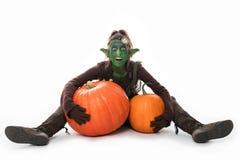 Θηλυκό πράσινο goblin με τις κολοκύθες, αποκριές Στοκ Φωτογραφίες