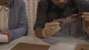 Θηλυκό πρωτόκολλο πλήρωσης εγκληματολόγων ενώ ο άνδρας συνάδελφός της που εξετάζει τα στοιχεία απόθεμα βίντεο