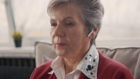 Θηλυκό πρόσωπο κατά τη στενή άποψη με τα ασύρματα ακουστικά bluetooth για τη σύγχρονη επαγγελματική εργασία φιλμ μικρού μήκους