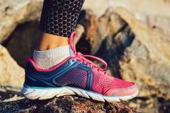 Θηλυκό πόδι στο ρόδινο και μπλε πάνινο παπούτσι που στέκεται στις δύσκολες πέτρες Στοκ εικόνα με δικαίωμα ελεύθερης χρήσης