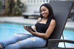 Θηλυκό σε διακοπές που μένουν συνδεμένες με την επιχείρηση με μια ταμπλέτα στοκ φωτογραφία με δικαίωμα ελεύθερης χρήσης