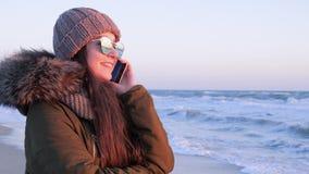 Θηλυκό στα γυαλιά ηλίου που μιλούν στο κινητό τηλέφωνο σε υπαίθριο στις διακοπές στην παραλία απόθεμα βίντεο