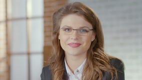 Θηλυκό στα γυαλιά που εξετάζουν τη κάμερα και που χαμογελούν, άνθρωποι επιχειρησιακών κόσμων, αξιόπιστοι απόθεμα βίντεο