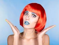 Θηλυκό στην κόκκινη περούκα και στο κωμικό λαϊκό ύφος σύνθεσης τέχνης στην μπλε ΤΣΕ Στοκ Φωτογραφία