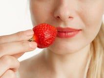 Θηλυκό στόμα με τα μούρα φραουλών δοντιών σε ένα άσπρο υπόβαθρο στοκ εικόνα με δικαίωμα ελεύθερης χρήσης